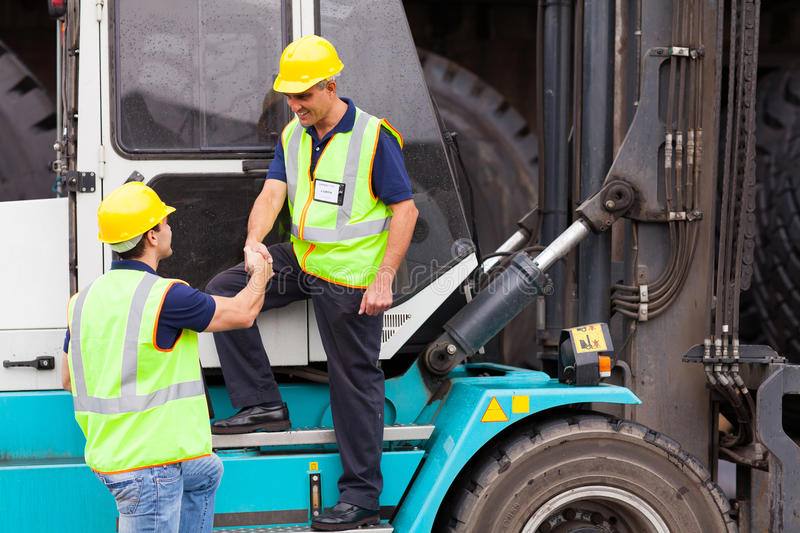 Driver handshaking colleague. Smiling forklift driver handshaking with colleague royalty free stock photography