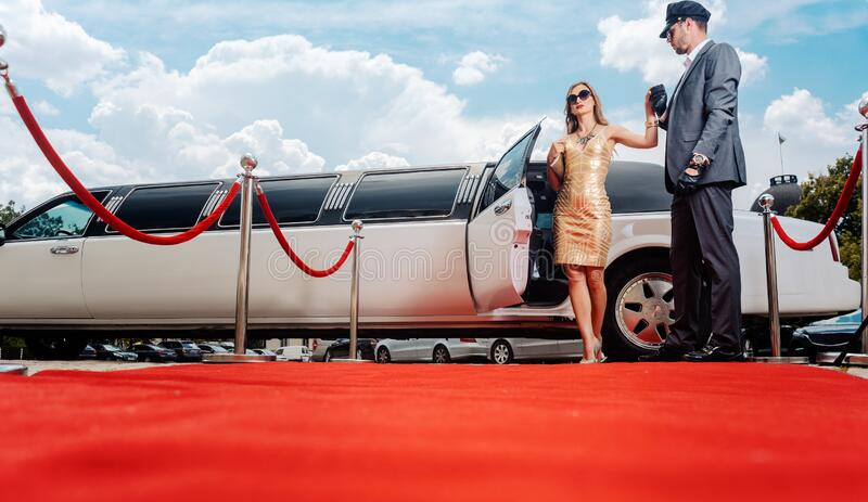 Driver helping VIP woman or star out of limo on red carpet royalty free stock images