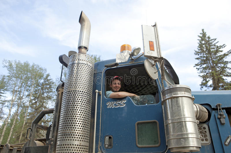 A driver with his truck, Alberta, Canada. A driver leaning against his window opening of his truck, Alberta, Canada stock image