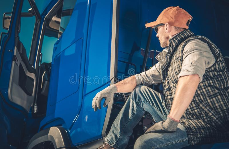 The Driver and His Truck. Caucasian Trucker in His 30s Taking a Break Seating on His Semi stock photography