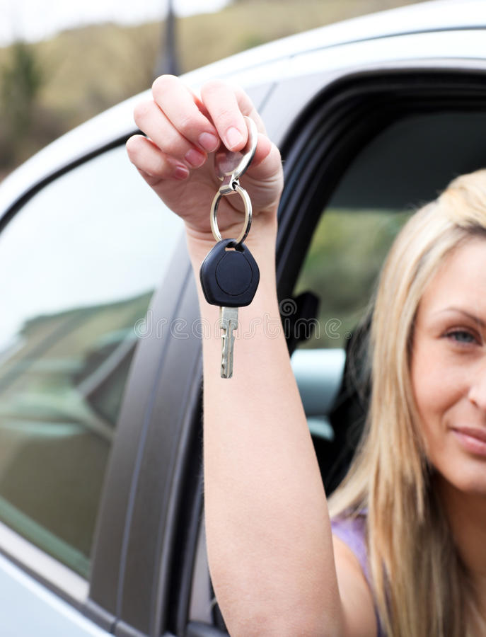 A driver holding a key after buying a new car. Close-up of a driver holding a key after buying a new car stock photography