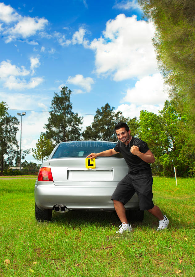 Driver holding learner licence plates beside car royalty free stock photography
