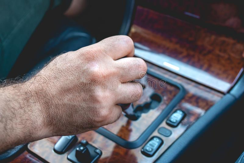 Driver man hand holding automatic transmission in car. Male hand changing levels of automatic gearbox in the car. Transportation stock photography
