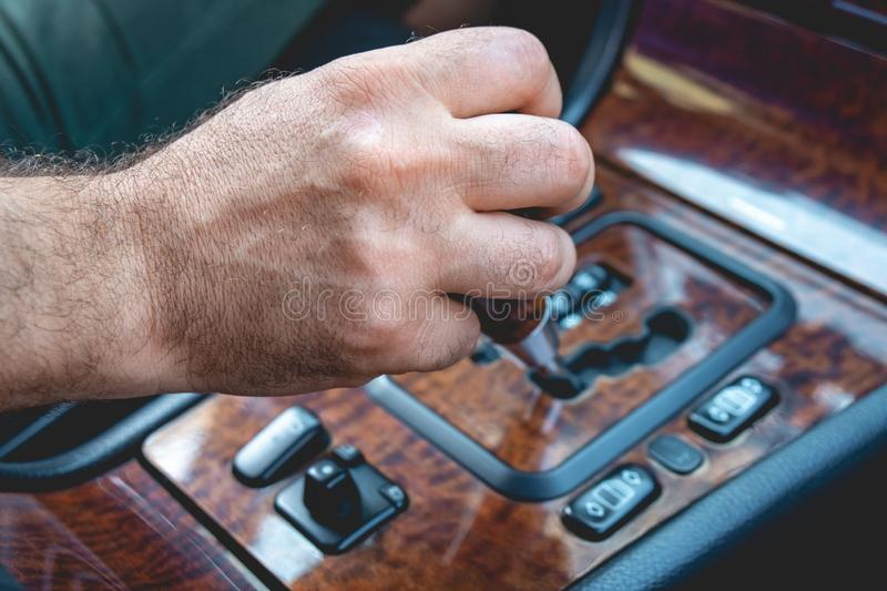 Driver man hand holding automatic transmission in car. Male hand changing levels of automatic gearbox in the car. Transportation royalty free stock photos