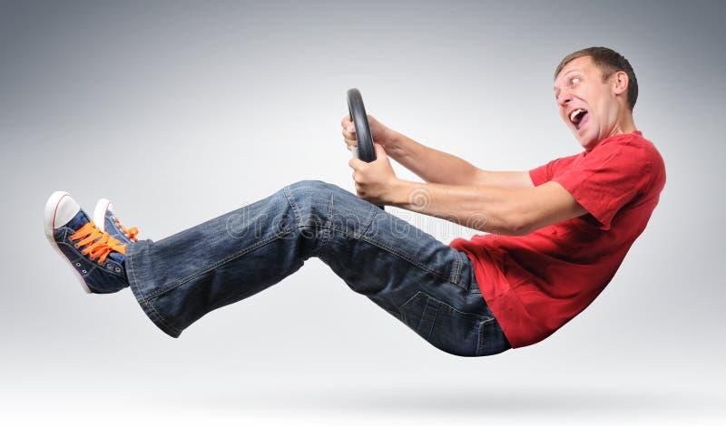 Driver maschio divertente con il concetto della rotella immagine stock