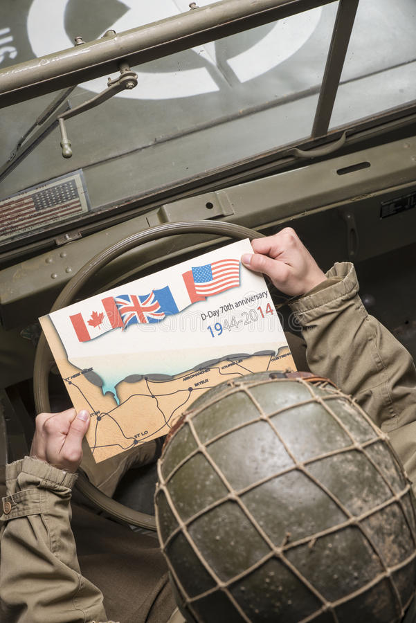 Driver of a military vehicle look at a map of Normandy. For the 70th anniversary royalty free stock photo
