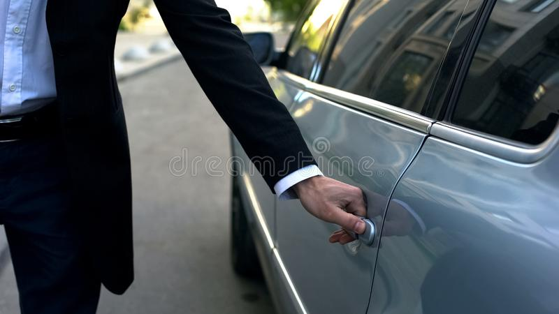 Driver opening car door to young respectable oligarch, professional chauffeur royalty free stock photos