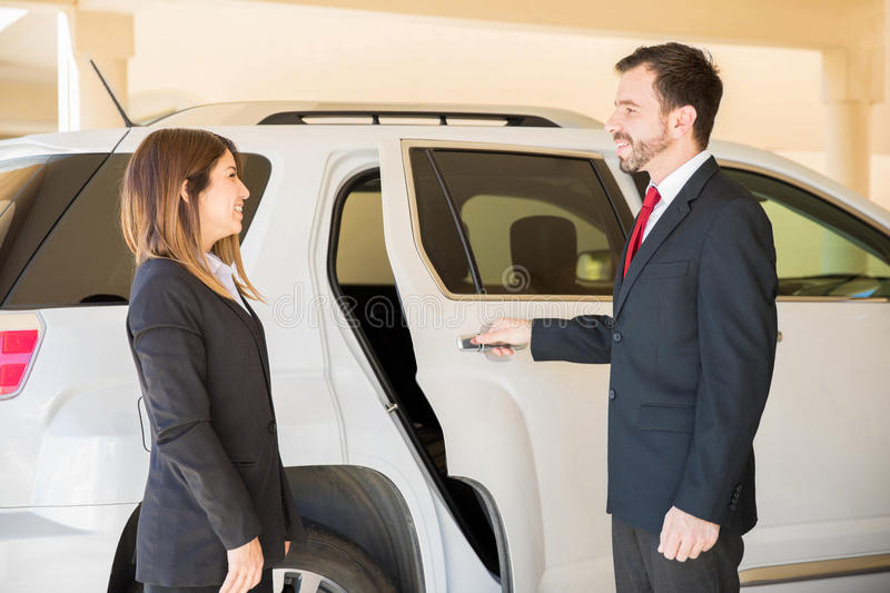 Driver opening door to businesswoman royalty free stock photos
