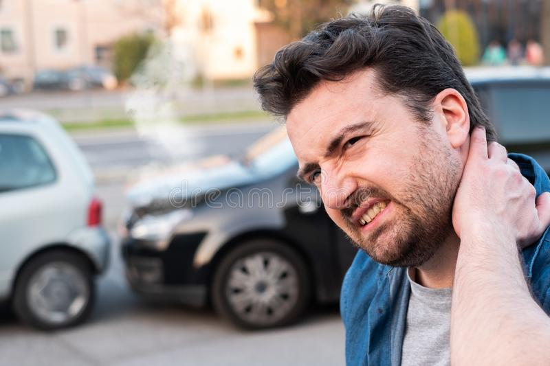 Driver portrait feeling pain after car accident. Driver injured after one bad car crash royalty free stock photography
