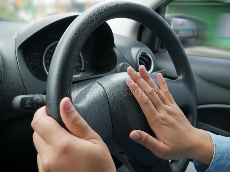 Driver Pressing Car Horn. Female driver steering a car and press car horn, honking soung to warn other people in traffic vehicle hand wheel auto road automobile stock image