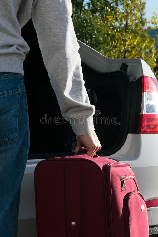 The driver puts the suitcases of the rest in the trunk of the car stock photography