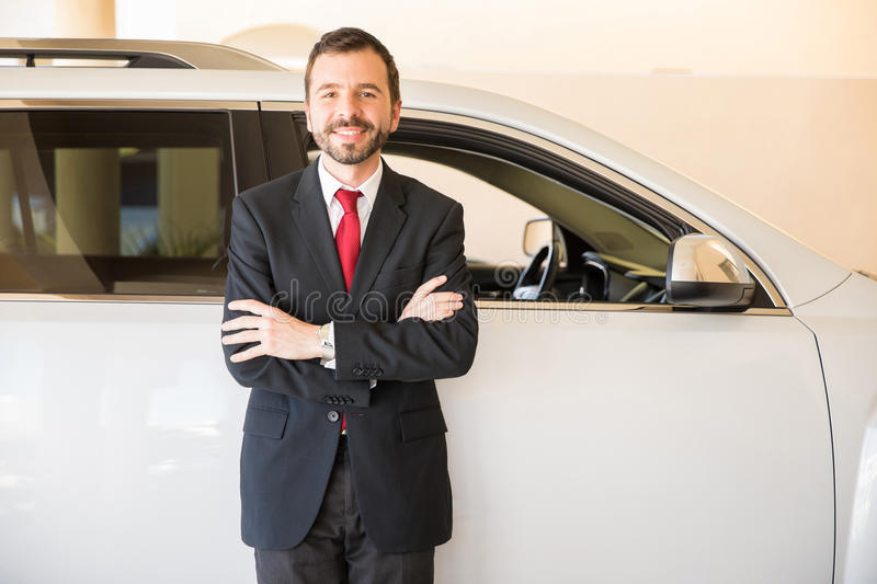Driver ready to take you to your destination. Portrait of a handsome young Hispanic male driver ready to take his clients anywhere they need to in his car royalty free stock photos
