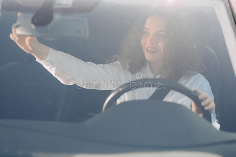 Driver in rear-view mirror. Attractive young woman in business wear looking in rear-view mirror and smiling while driving a car royalty free stock photos