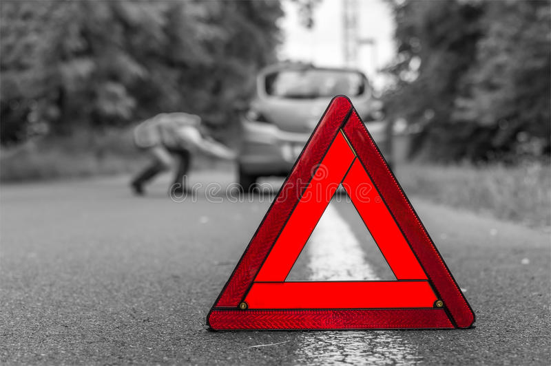 Driver in reflective vest changing tire and red triangle stock images