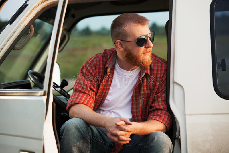 Driver sits in his truck cab. Bearded driver sits in his truck cab royalty free stock photos