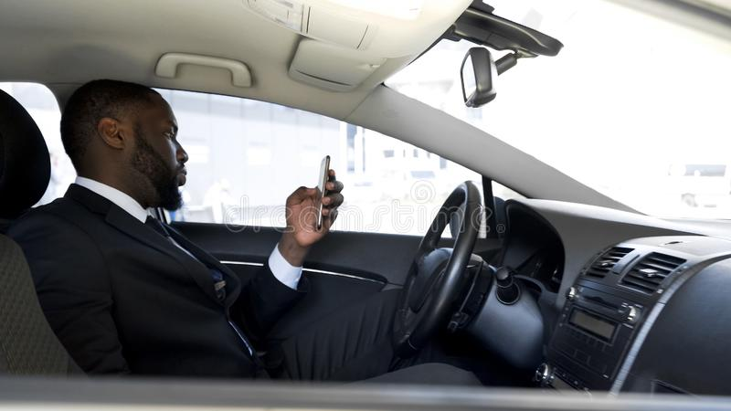 Driver sitting in car parked near airport checking schedule of boss airplane stock photo
