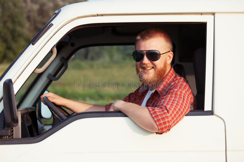Driver of a small pickup truck. Cheerful driver of a small pickup truck stock image