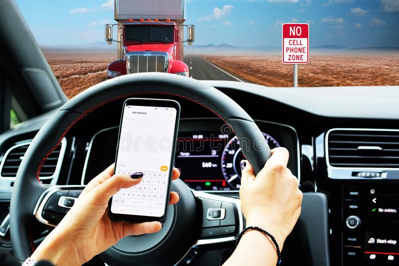 Driver spensierato che manda un sms mentre guidando sulla strada campestre vuota fotografia stock