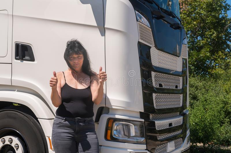 Driver of the truck shows both thumbs up. Driver stands in front of her truck and shows both thumbs up stock images