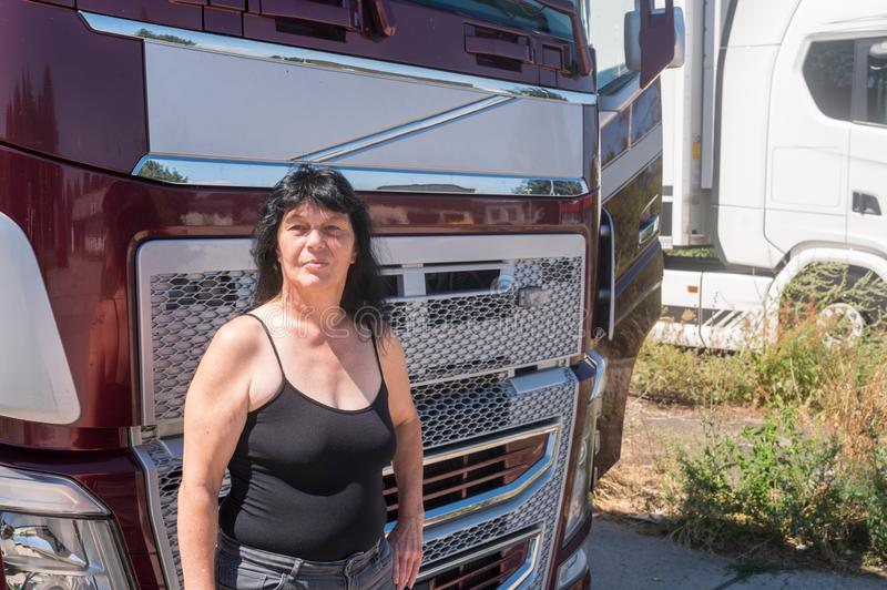 Driver stands in front of her truck. Driver stands proudly in front of her truck in sunshine stock images