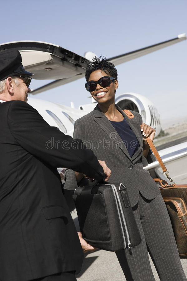 Driver Taking Briefcase From Business Woman At Airfield royalty free stock photos