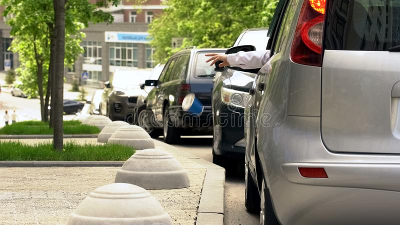Driver throwing trash out of car window, contamination in city, dirty sidewalks royalty free stock images