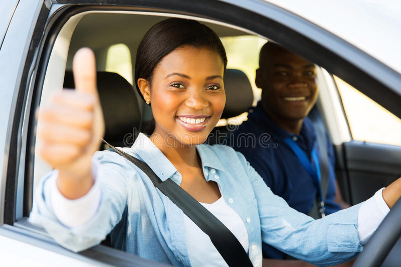 Driver thumb up. Beautiful female african learner driver with instructor giving thumb up stock photos