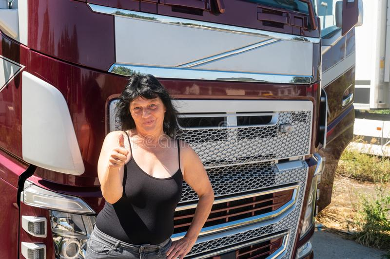 Driver of a truck shows thumbs up. The driver of a truck stands in front of the truck and shows her thumbs up stock images