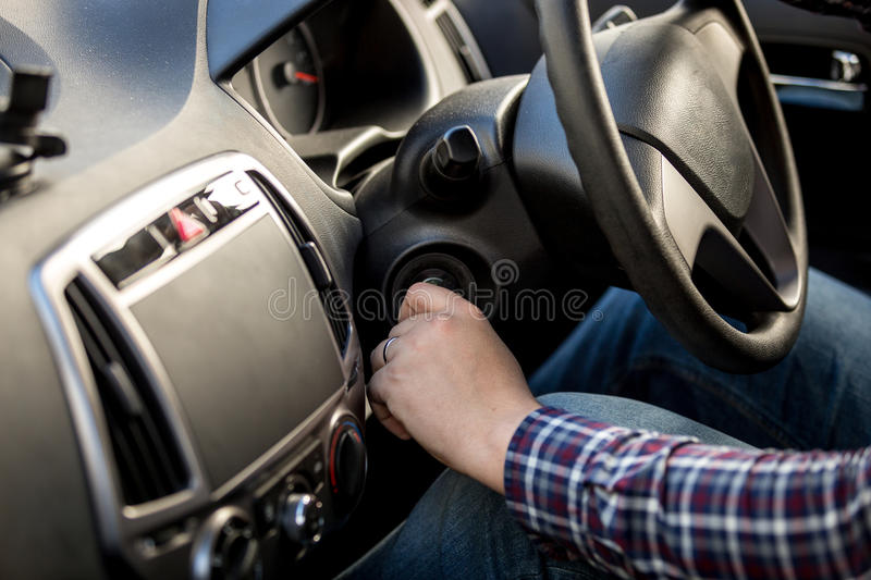 Driver turning ignition key in right-hand drive car. Male driver turning ignition key in right-hand drive car royalty free stock image