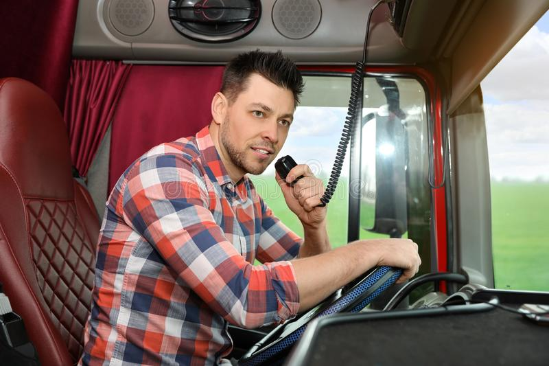 Driver using CB radio in cab of truck. Driver using CB radio in cab of modern truck royalty free stock image