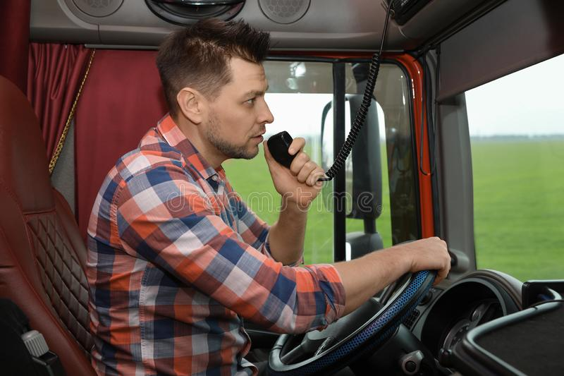 Driver using CB radio in cab of truck. Driver using CB radio in cab of modern truck royalty free stock photos