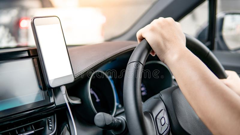 Driver using mobile app for GPS navigation. Male driver hand holding on steering wheel using smartphone for GPS navigation. Mobile phone mounting with magnet on stock image