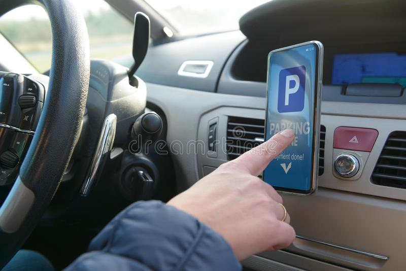 Driver using smartphone app to pay for parking royalty free stock photo