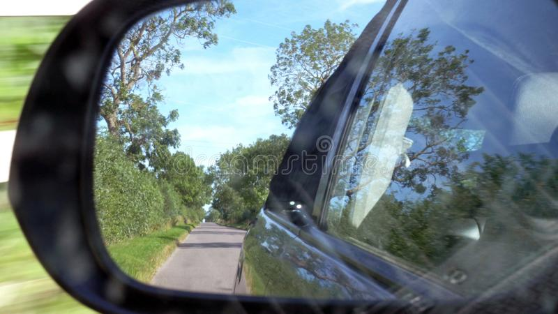 Driver view pov shot through car mirror driving on british road in england.  stock images