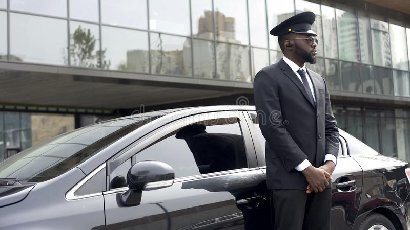 Driver of vip hotel service waiting for passengers near his car, ready to go. Stock photo stock photography