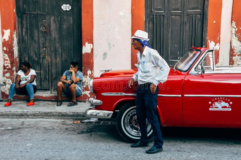 A driver waits for his clients by his classic car in Havana, Cuba. A driver waits for his clients by his red classic car in Havana, Cuba royalty free stock images