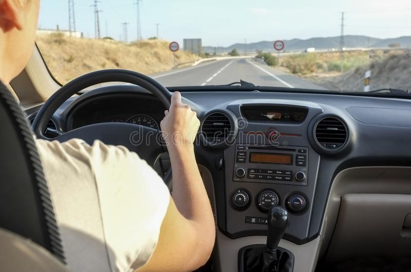 Driver woman getting close to no overtaking area at country road. Inside car view stock photography