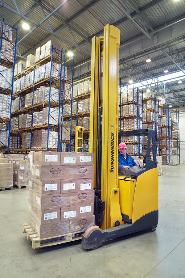 Driver of yellow forklift truck operates, in warehouses. St. Petersburg, Russia - November 21, 2008: The driver of a yellow forklift truck operates, in stock photo