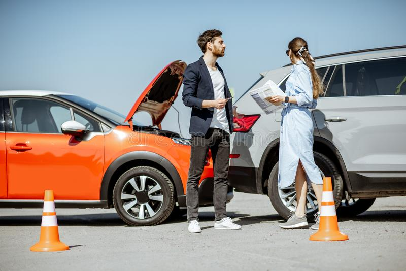 Drivers after the car accident. Man and women arguing, standing together on the road with their cars on the background after the car accident stock images