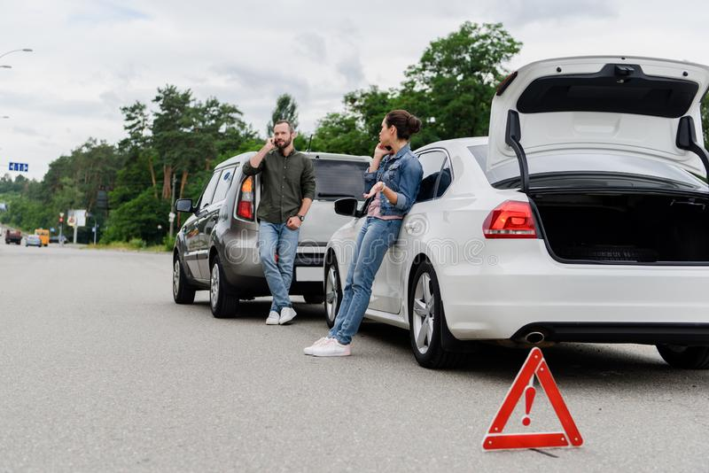 Drivers talking by smartphones on road after. Car accident stock photography