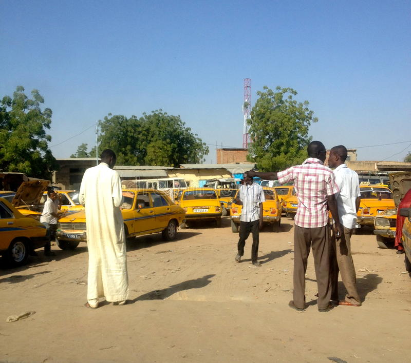 Drivers at a taxi stand, N'Djamena, Chad. Drivers talking at a taxi stand, with yellow cars. One guy in local clothing royalty free stock image