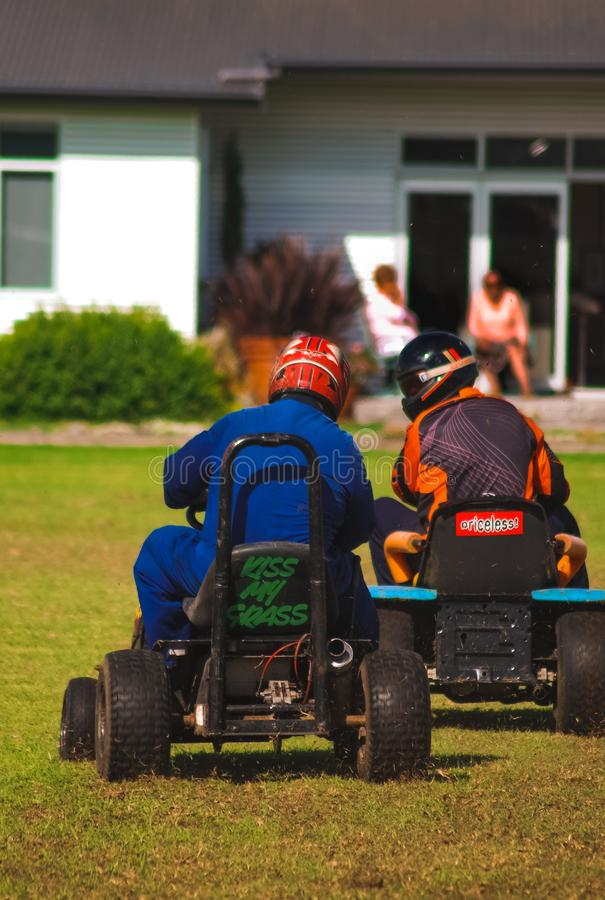 Drivers on trimmed lawnmowers. A couple of drivers participating in a lawnmower race stock images