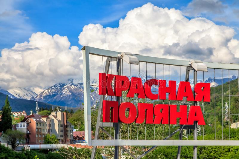 Driveway sign of Krasnaya Polyana ski mountain resort. Resort`s name on scenic green forest and mountain background stock photos