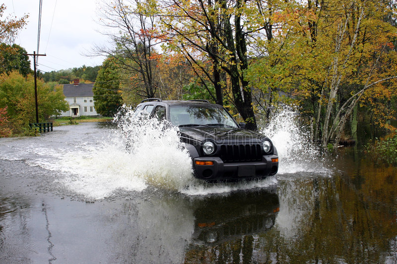 Driving Through #2. Image of driver fording through flooded roadway in New England