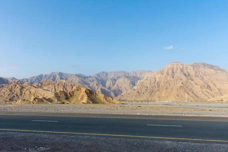 Driving along Jebal Jais Mountain road in Ras al Khaimah, United Arab Emirates UAE as the sun sets against the rocky mountains. With a blue sky royalty free stock photo