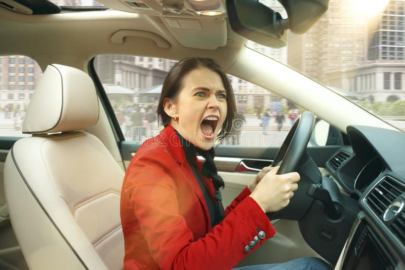 Driving around city. Young attractive woman driving a car stock images