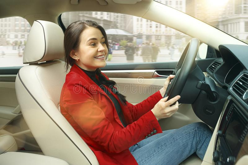 Driving around city. Young attractive woman driving a car stock photos