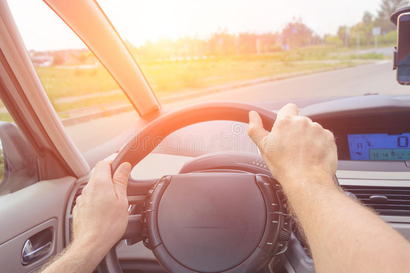 Driving a car - first person view. Hands on steering wheel royalty free stock photos