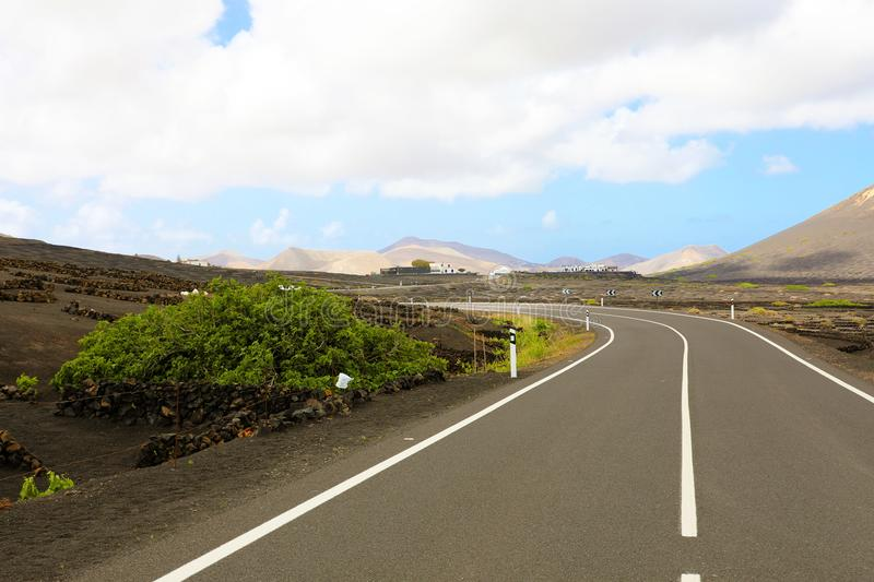 Driving a car on Lanzarote island road. Asphalt road curved among vineyards with black ground and volcanos on the background. Beautiful street with natural royalty free stock image