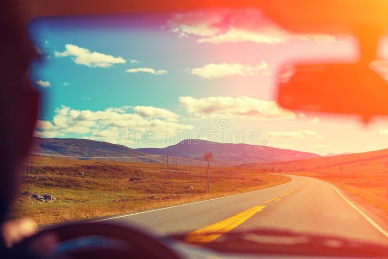 Driving a car on the mountain road at sunset royalty free stock photos